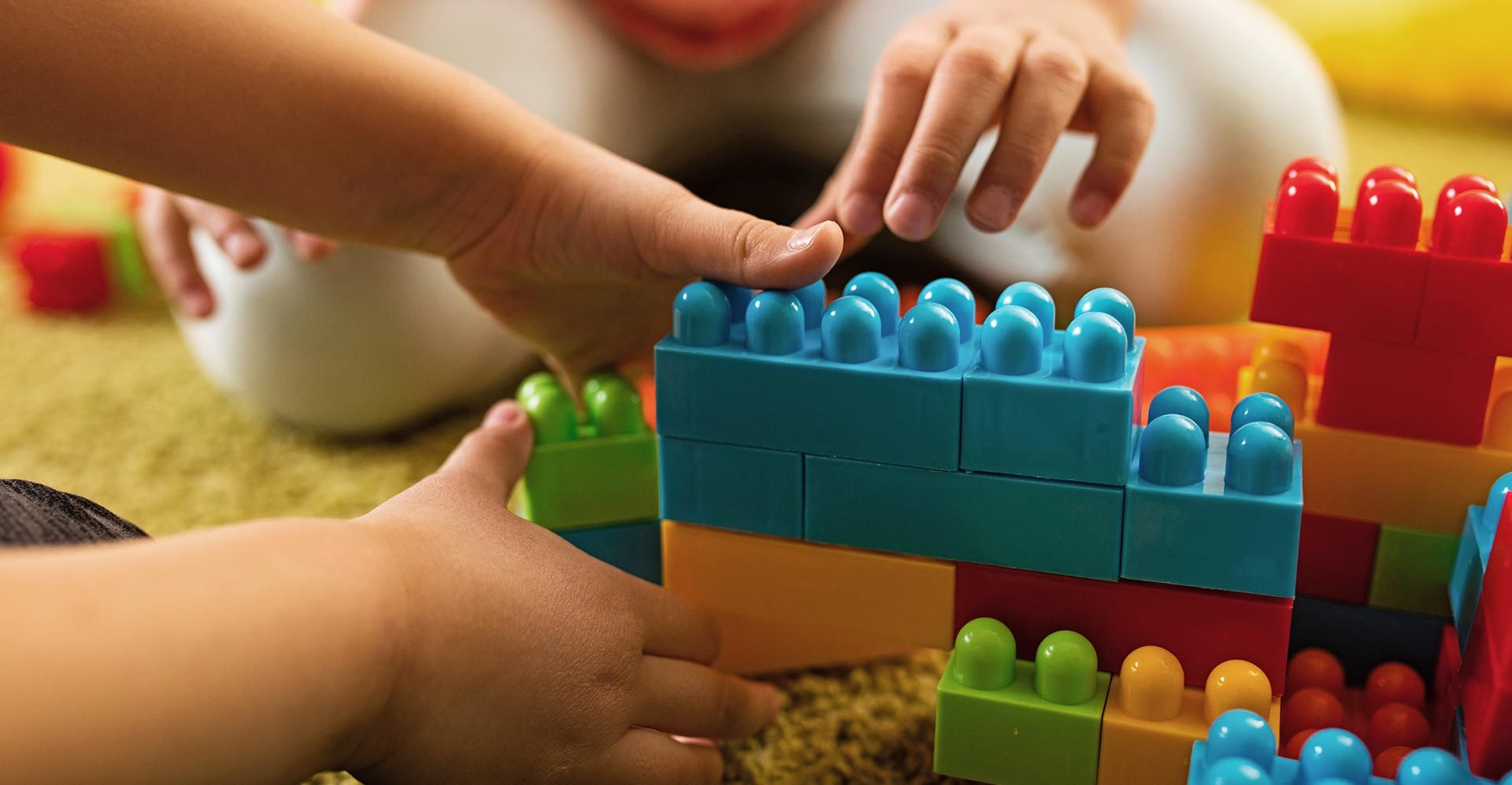Children playing with colorful toy blocks