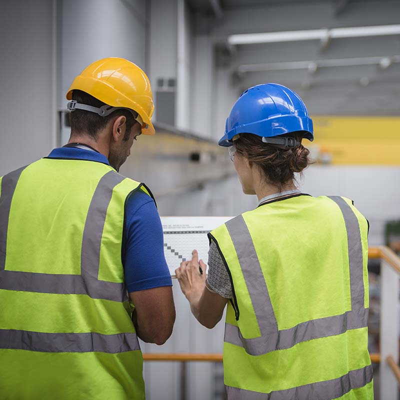 Employees in safety vests and helmets checking paperwork